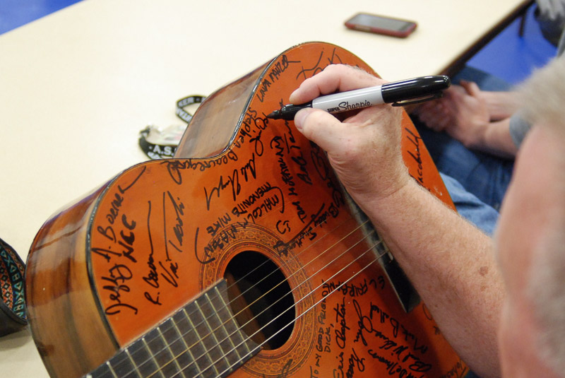 man adding signature to many already on a guitar