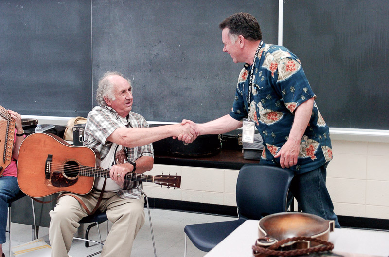 two men shake hands before playing music together
