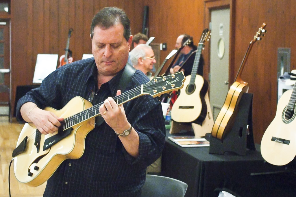 man playing an archtop guitar