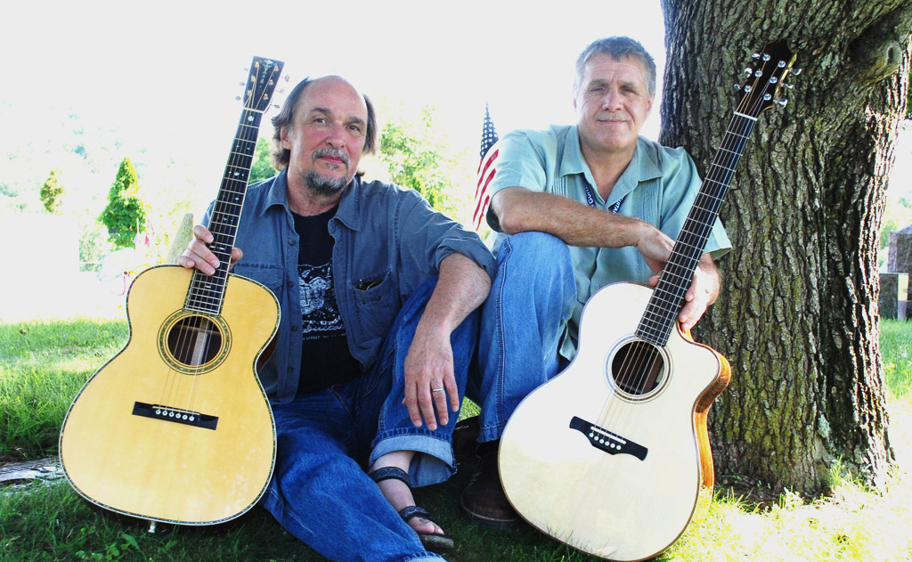 two men with guitars under a tree